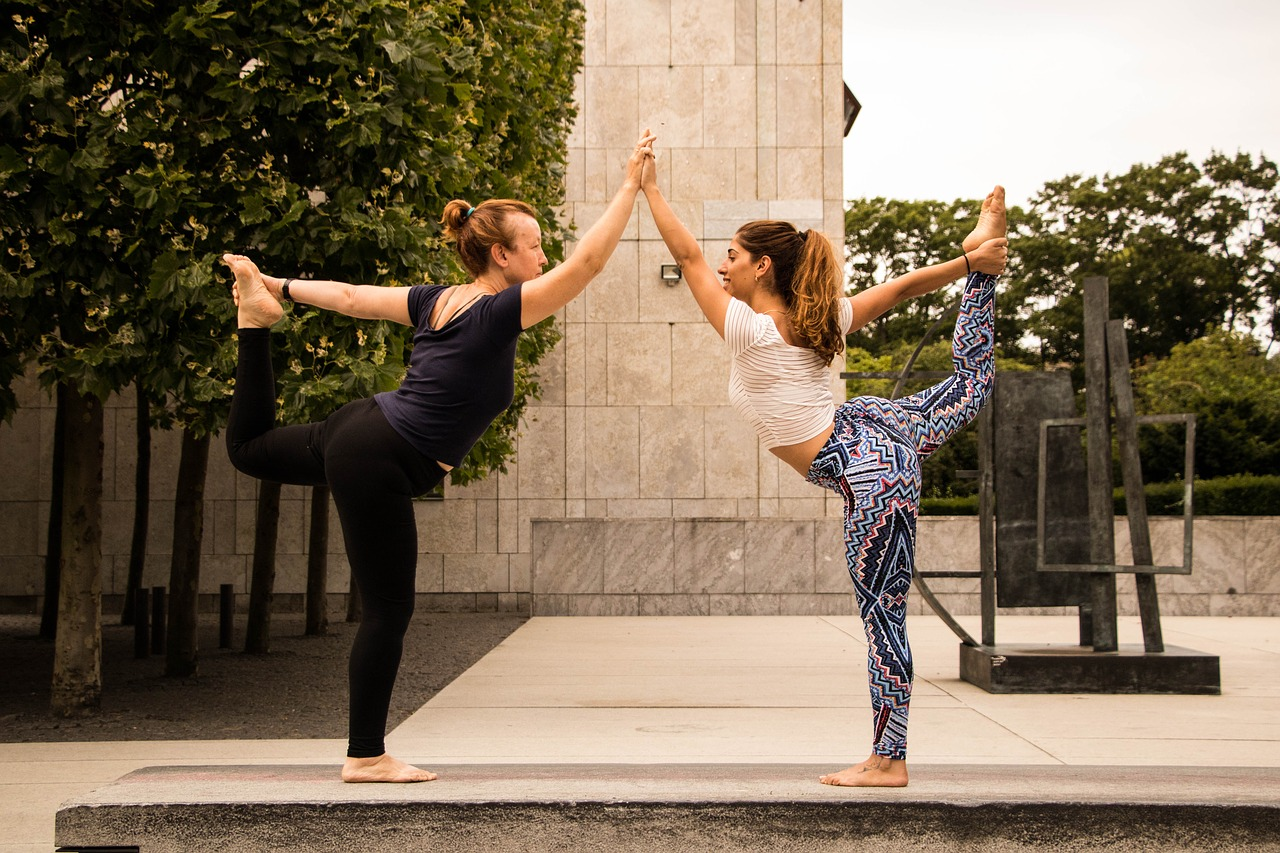 2-girls-performing-yoga-together-on-street
