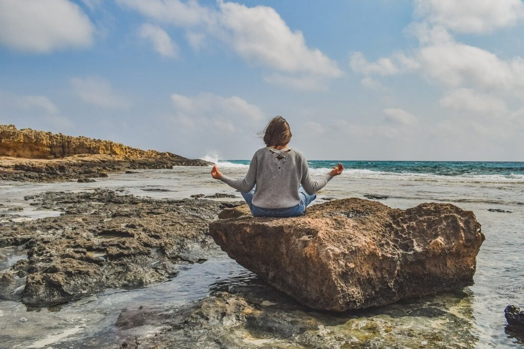girl-practicing-meditation-on-rocky-beach