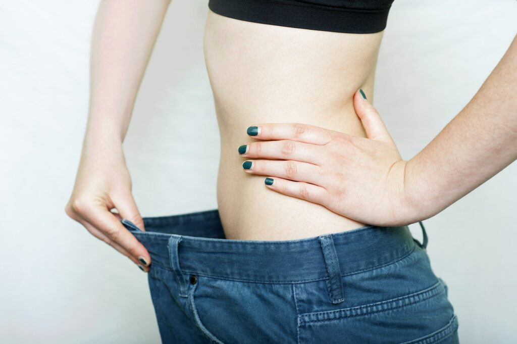girl-showing-her-reduced-waist-as-a-sign-of-weight-loss